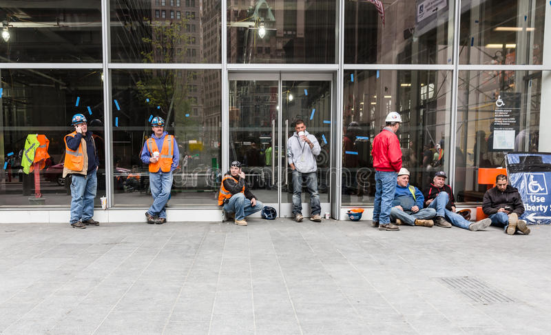 Group of construction workers having a break. NEW YORK, USA - Apr 28, 2016: Group of construction workers having a break on site in Lower Manhattan. Drinking royalty free stock photos