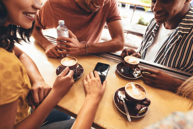 Discussing over new content. Group of creative people meeting up in at cafe and discussing over new content for their social media. Young men and women sitting stock photography
