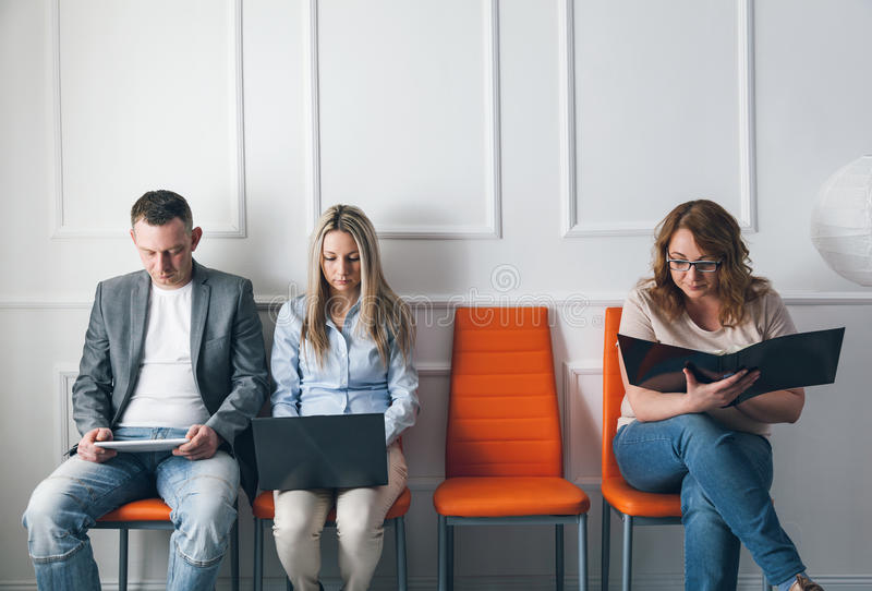 Download group of creative people sitting on chairs in waiting room stock photo image of