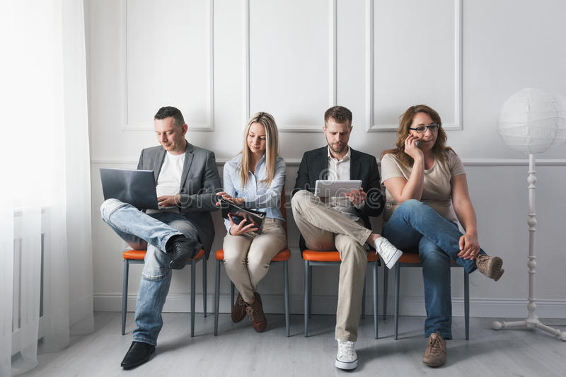 Group of creative people sitting on chairs in waiting room stock photos