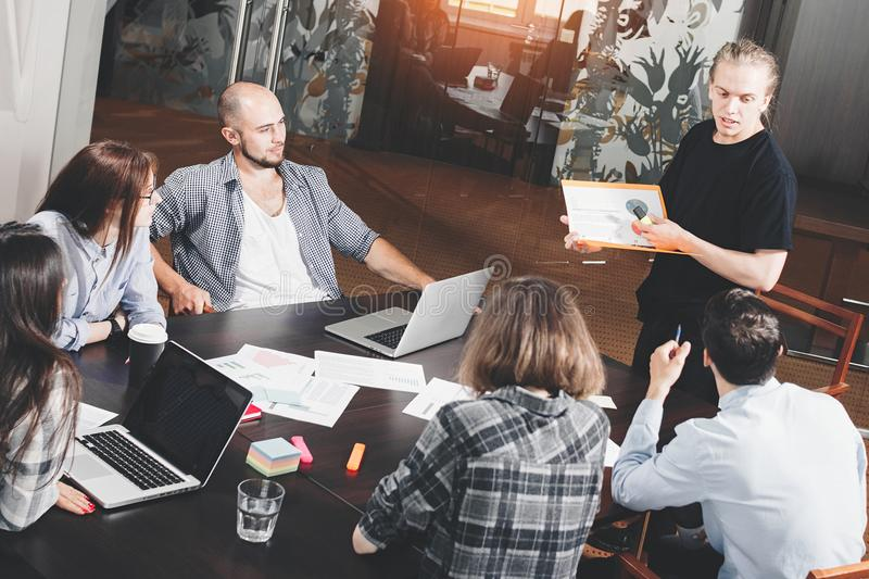 Group of creative project managers analyzes development of startup. Business people work for papers and laptop in loft space stock photo