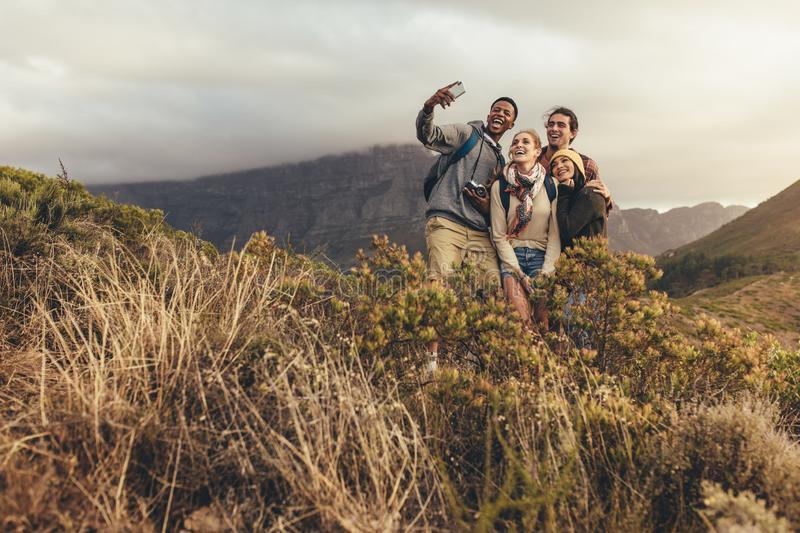 Group of creatives on hiking trip. Taking selfie to create new content for social media. Young men and women hiking together on mountain trail with a male royalty free stock photography