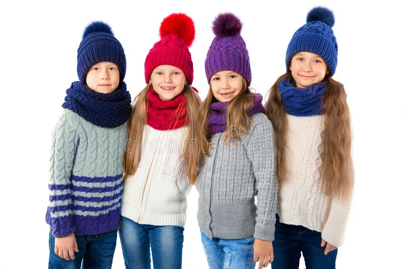 Group of cute kids in winter warm hats and scarfs on white. Children winter clothes. Group of cute kids in winter warm hats and scarfs on a white background stock photos