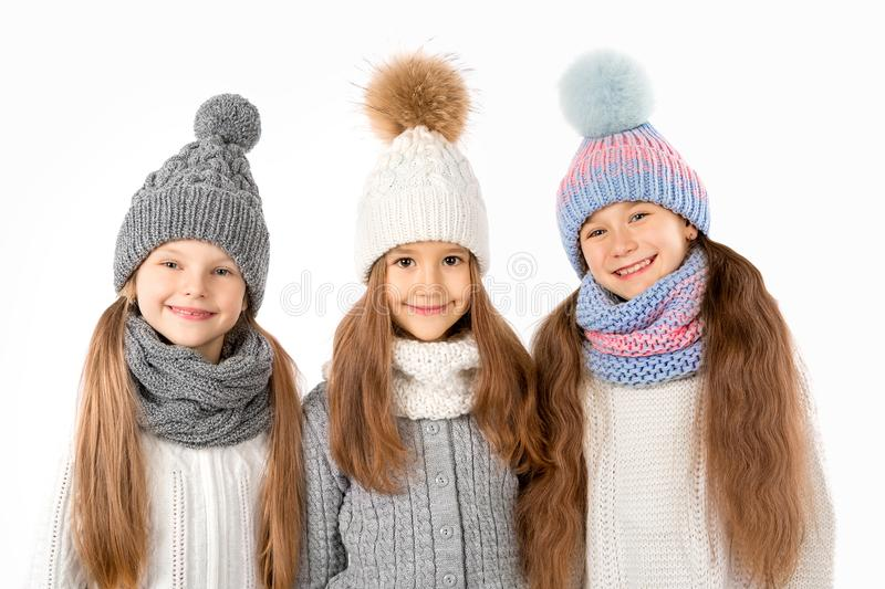 Group of cute kids in winter warm hats and scarfs on white. Children winter clothes. Group of cute kids in winter warm hats and scarfs on a white background royalty free stock images