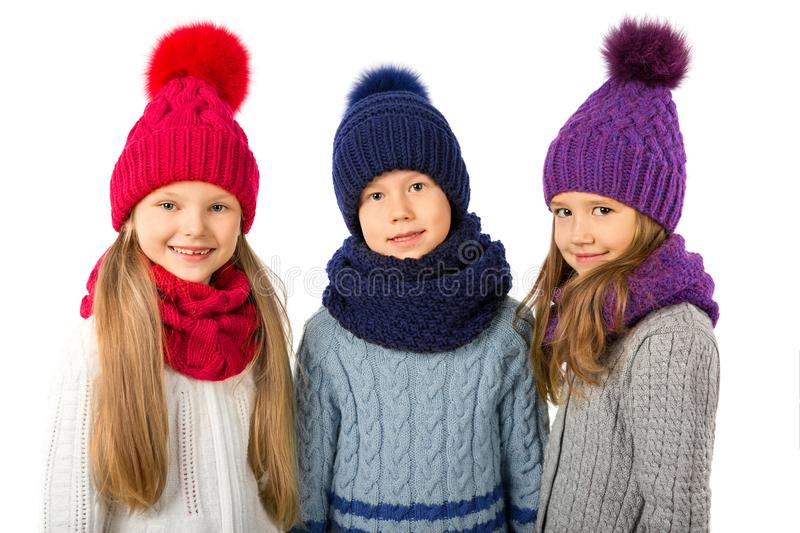 Group of cute kids in winter warm hats and scarfs on white. Children winter clothes. Group of cute kids in winter warm hats and scarfs on a white background royalty free stock photography