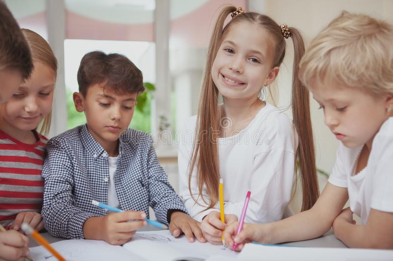 Group of cute little kids drawing together in art class. Cheerful beautiful little girl smiling to the camera while drawing at art class with her classmates stock photo