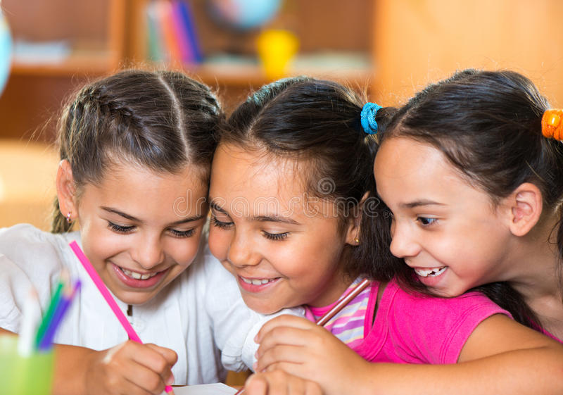 Group of cute schoolchildren having fun in classroom stock photos