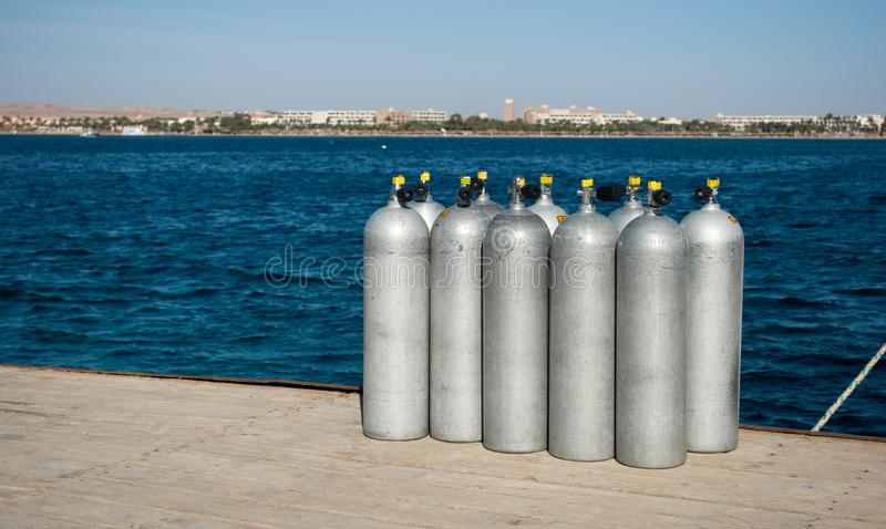 Cylinders with helium on dock. ten white cylinders for divers on sea dock. oxygen tanks for divers on pier. Group cylinders with helium on dock. ten white royalty free stock image