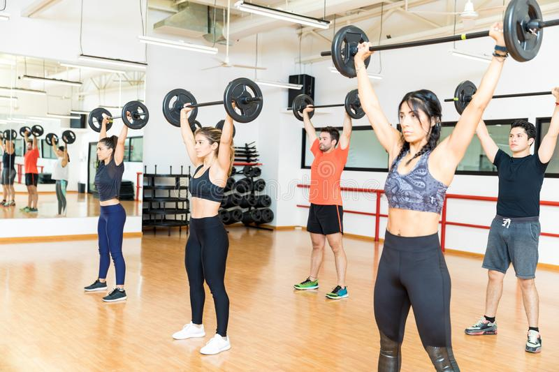 Determined Men And Women Lifting Barbells In Gym stock images