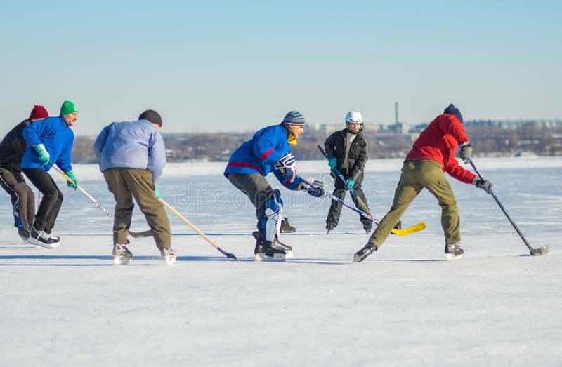 Group of different ages people playing hockey on a frozen river Dnepr in Ukraine. Dnepr, Ukraine - January 22, 2017: Group of different ages people playing royalty free stock image