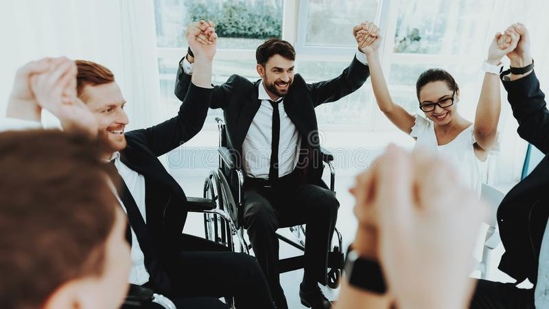 Group Disabled People Raise Hands in Bright Office. Collective Work. Group Disabled Worker. Workers with Disabilities. Business Meeting. Business Suits. Disabled royalty free stock photography