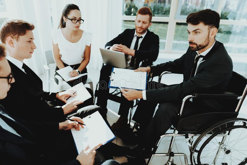 Group Disabled Worker with Papers in Bright Office stock photography