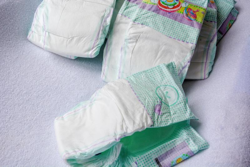 Group of disposable diapers arranged over a white changing table royalty free stock image