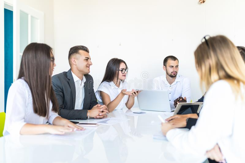 Group of diverse business executives holding a meeting around a table discussing graphs showing statistical analysis. Team work stock photography