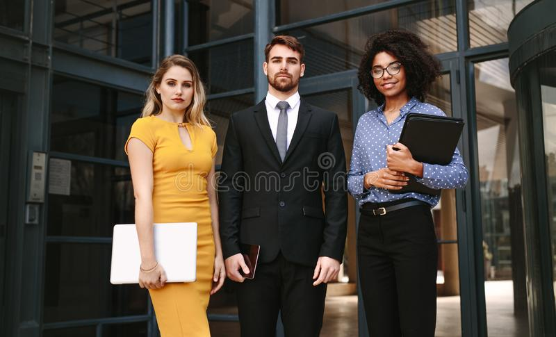 Group of diverse business professionals. Portrait of three business people standing together in front of office building. Group of diverse business professionals royalty free stock images