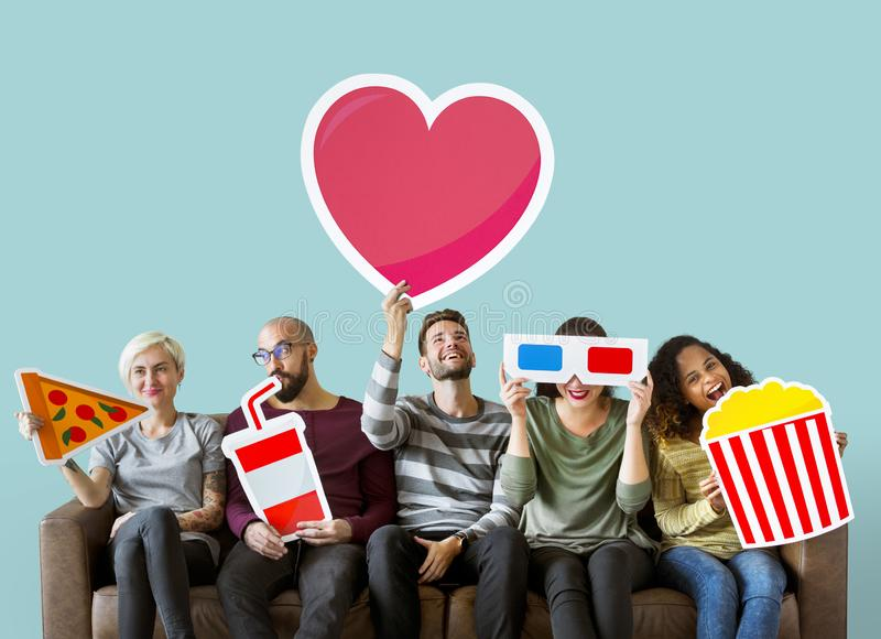 Group of diverse friends holding movie emoticons stock photography
