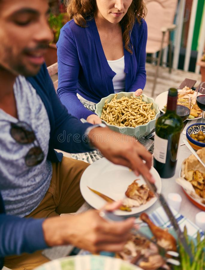 Group of diverse friends serving a balanced dinner al fresco in stock image