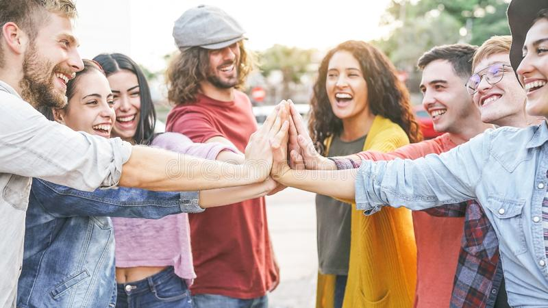 Group of diverse friends stacking hands outdoor - Happy young people having fun joining and celebrating together stock image