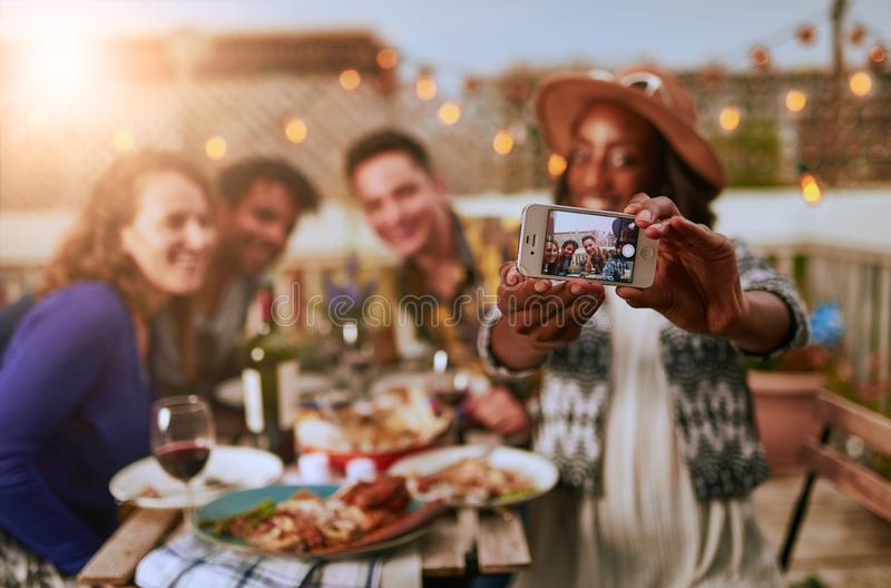 Group of diverse friends taking selfies pictures having dinner a stock photo
