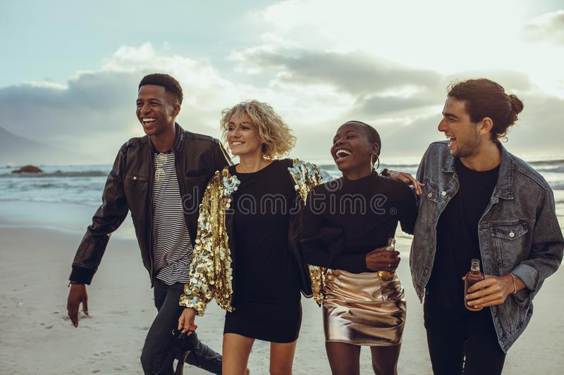 Group of diverse friends walking at the beach. Four friends strolling at the beach stock image