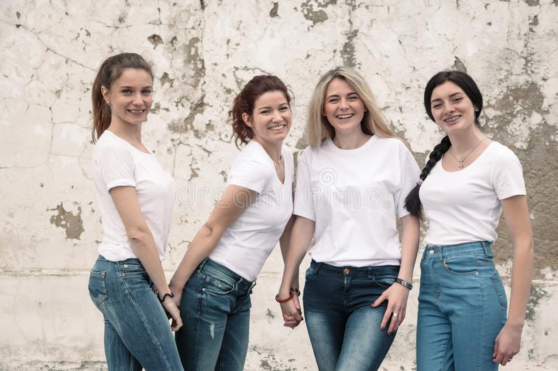 Group of diverse girls in tshirts and jeans over street wall royalty free stock image