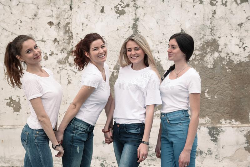 Group of diverse girls in tshirts and jeans over street wall royalty free stock photo