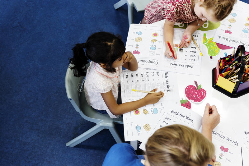 Group of diverse Kids coloring workbook in class stock photos