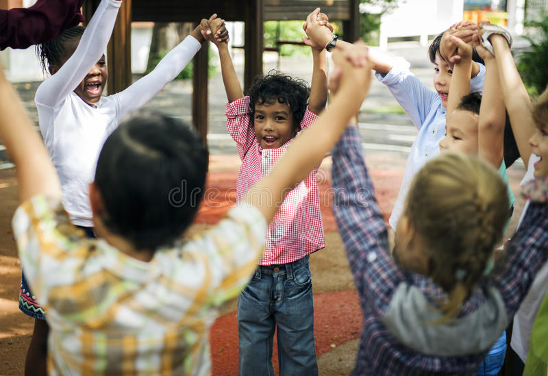 Group of diverse kindergarten students hands up together royalty free stock image