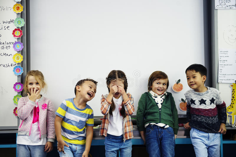 Group of diverse kindergarten students standing together in classroom stock images