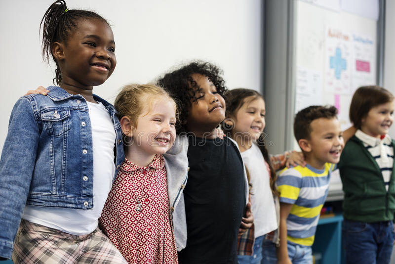 Group of diverse kindergarten students standing together in classroom royalty free stock photography