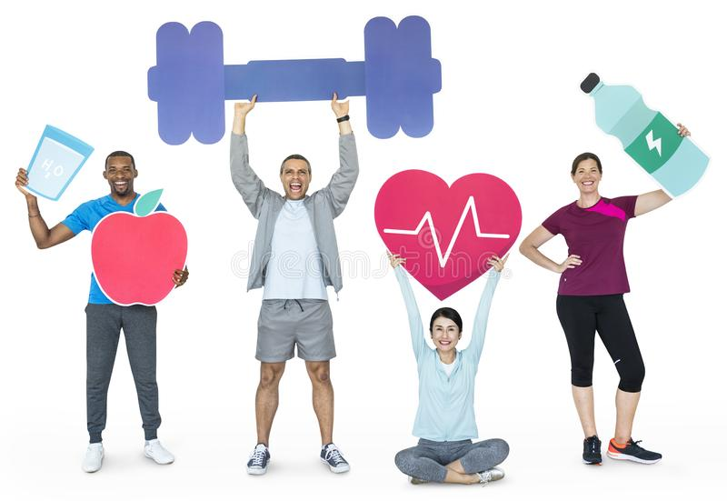 Group of diverse people holding health and fitness icons royalty free stock photography