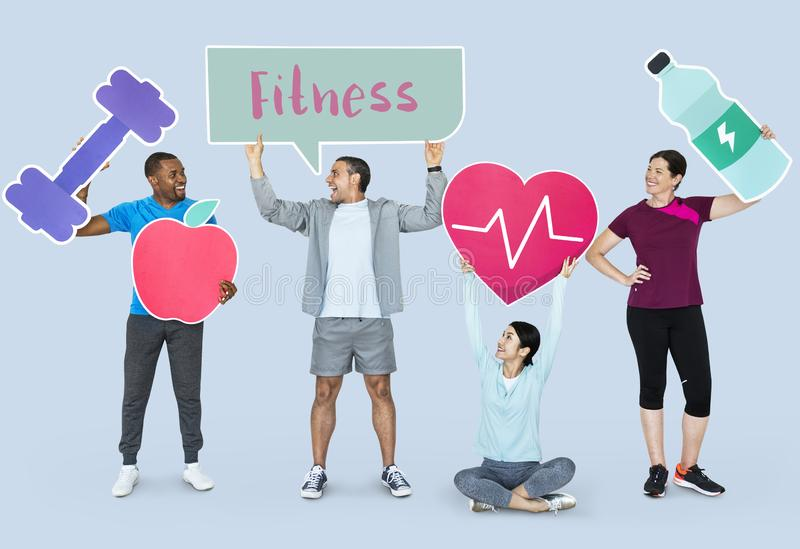 Group of diverse people holding health and fitness icons stock photos
