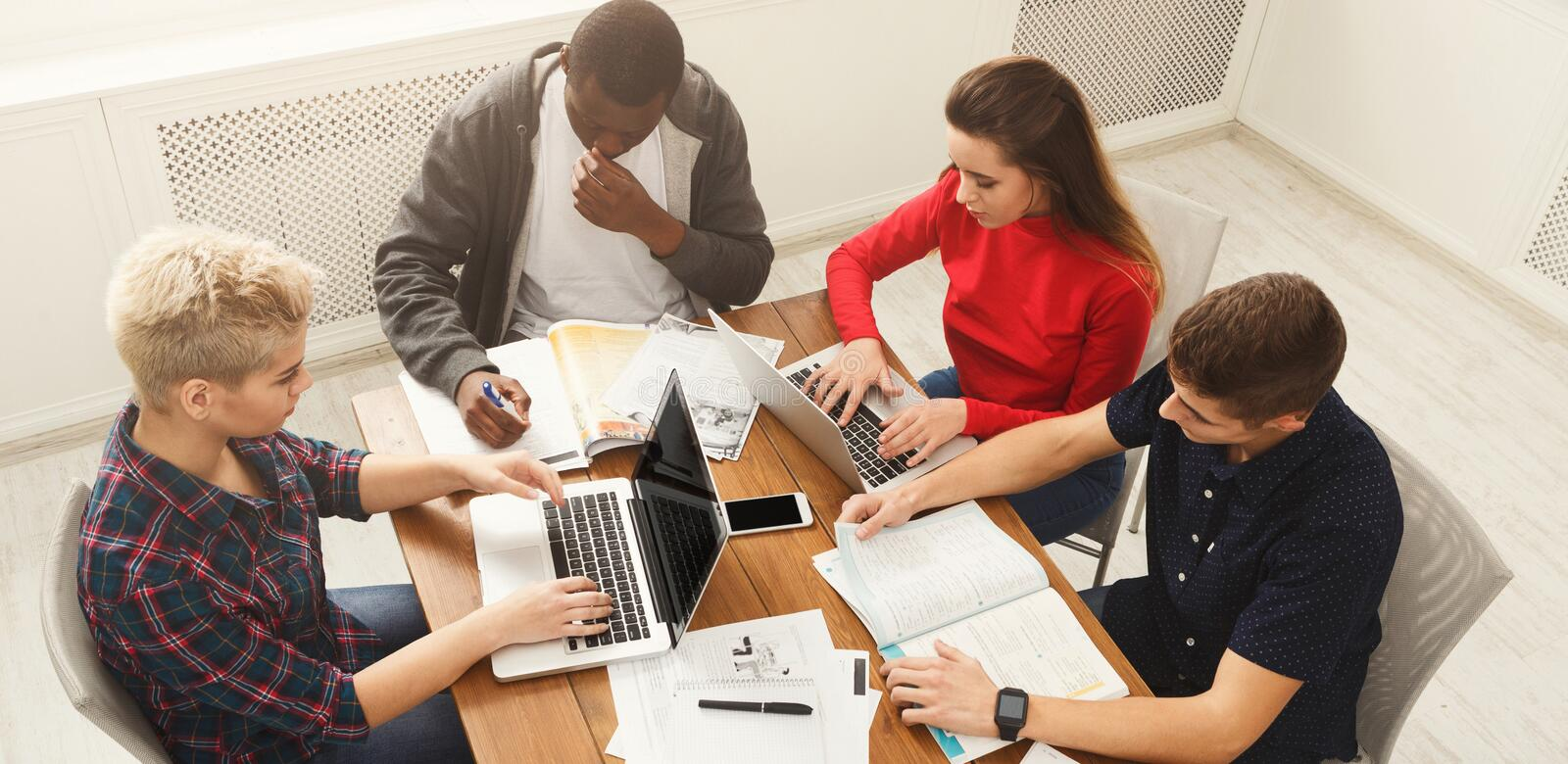 Group of diverse students studying at wooden table stock images