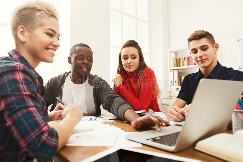 Group of diverse students studying at wooden table stock photos