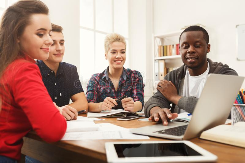 Group of diverse students studying at wooden table stock photo