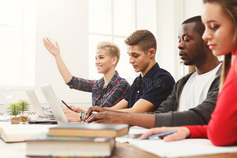 Group of diverse students studying at wooden table stock image