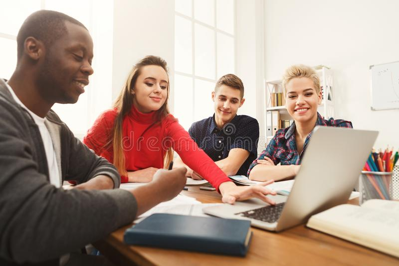 Group of diverse students studying at wooden table royalty free stock photos