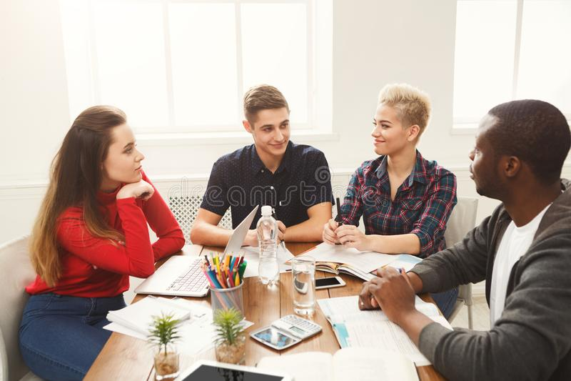 Group of diverse students studying at wooden table royalty free stock photography