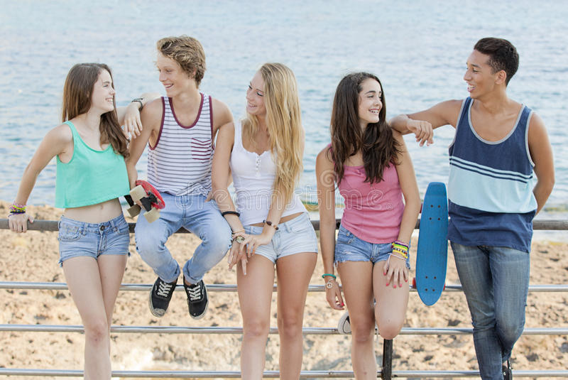 Group of diverse teens at beach stock image