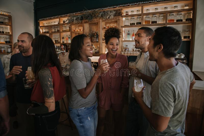 Diverse young friends enjoying an evening in a pub together stock photos