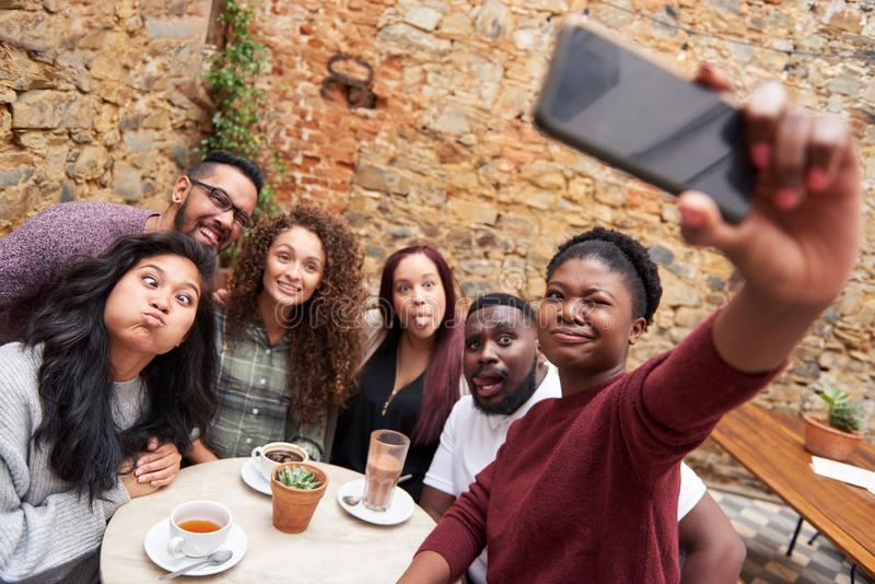 Friends making faces and taking selfies in a cafe courtyard royalty free stock photography