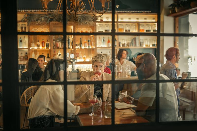 Diverse young friends having drinks together at a trendy bar royalty free stock photos