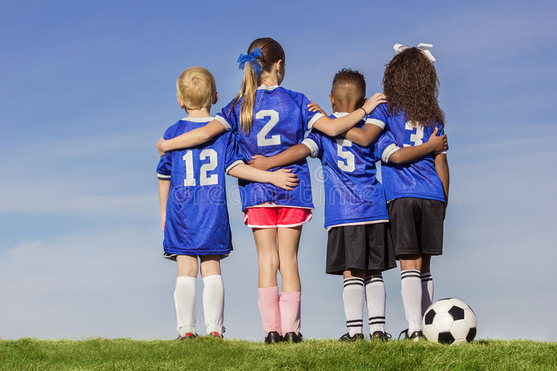 Group of Diverse young soccer players. Diverse group of boys and girls soccer players standing together with a ball against a simple blue sky background stock photography