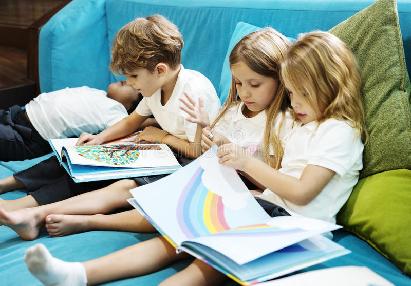 Group of Diverse Young Students Reading Children Story Book Together royalty free stock image