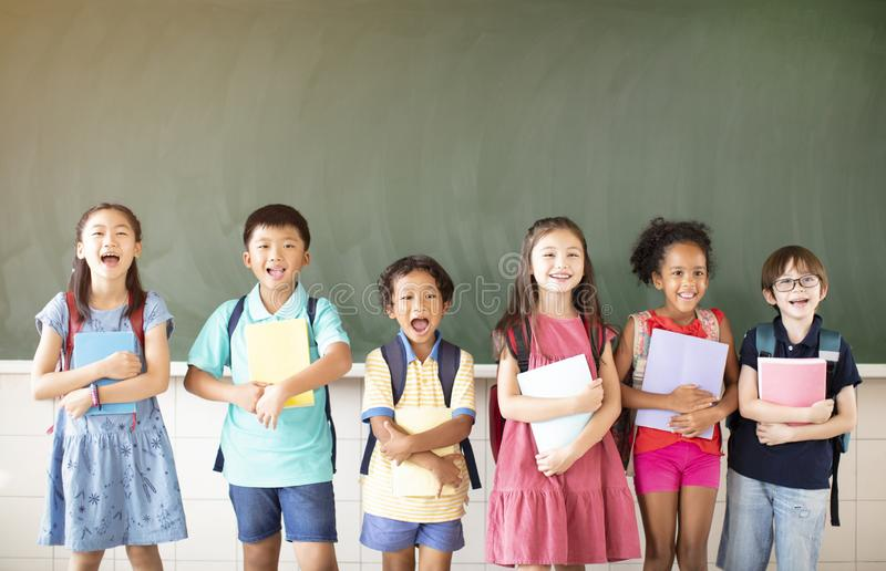 Diverse young students standing together in classroom stock image
