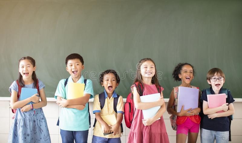 Diverse young students standing together in classroom stock photography
