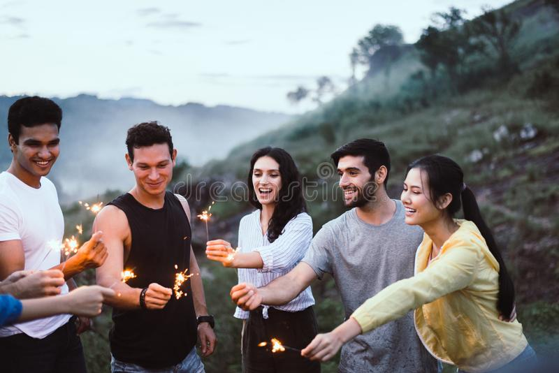 Group of diversity friends cheerful with sparklers and enjoying together at outdoor,Happy and smiling stock photo