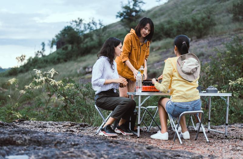 Group of diversity friend cooking food for dinner at outdoor together,Enjoying camping concept stock photo