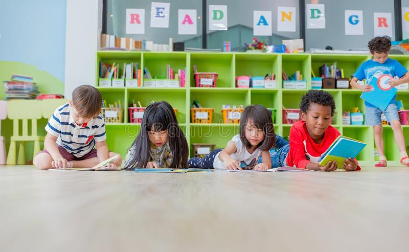 Group of diversity kid lay down on floor and reading tale book i. N preschool library,Kindergarten school education concept stock image