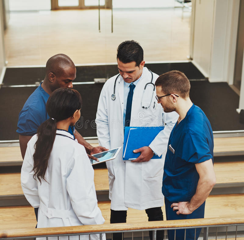 Group of doctors in an impromptu meeting. Multiracial group of doctors in an impromptu meeting standing on a stairwell looking at information on a tablet royalty free stock photos